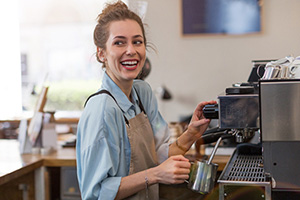 Young barista preparing coffee for customers at her cafe counter