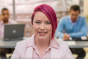 Portrait of businesswoman smiling in office, close-up.